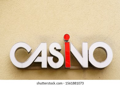 The closeup of a casino signboard on the yellow plaster of a facade.