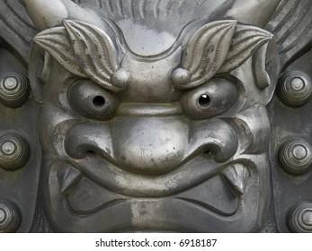 Close-up of cast iron metal face statue outside Tenryu-ji temple in Arashiyama in Kyoto, Japan