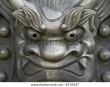 Close-up of cast iron metal face statue outside Tenryu-ji temple in Arashiyama in Kyoto, Japan