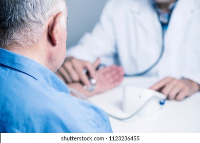 closeup of a caucasian doctor man, in a white coat, with measuring the blood pressure of a senior caucasian patient man with a sphygmomanometer