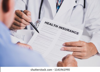 closeup of a caucasian doctor man, in a white coat, showing the clauses of a health insurance policy to a senior caucasian man, sitting both at his desk, at the doctors office