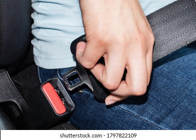 Close-up of a caucasian female hand holding a seat belt buckle for fastening in a car. Car safety concept