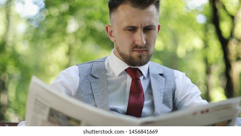 Close-up caucasian good looking sad businessman reading a newspaper in a park. A man with a beard resting outdoors.