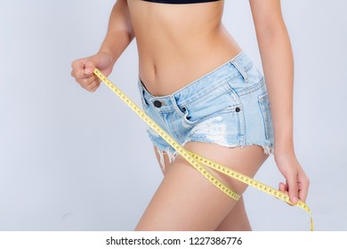 Closeup caucasian leg slim and body of woman with measure isolated on white background, girl with measuring centimeter  tape for healthy and diet, cellulite and calories for health care with perfect.