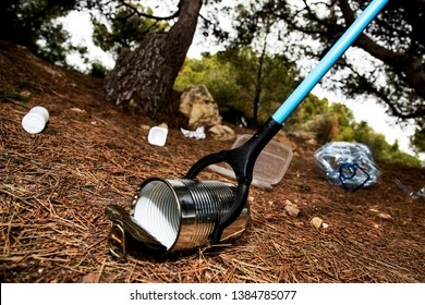 closeup of a caucasian man collecting garbage with a trash grabber stick, on a forest, as an action to clean the natural environment