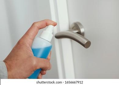 gros plan d'un homme caucasien désinfectant la poignée de la porte en vaporisant un nettoyant bleu d'une bouteille