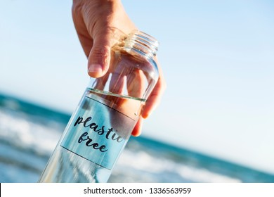 closeup of a caucasian man holding a glass reusable water bottle with the text plastic free written in it, on the beach, with the ocean in the background