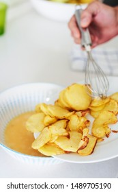 closeup of a caucasian man in the kitchen adding the fried potatoes to the beaten eggs, to prepare a typical tortilla de patatas, a spanish omelet