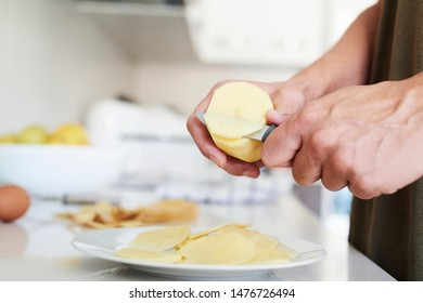 closeup of a caucasian man in the kitchen cutting some potatoes, to prepare a typical tortilla de patatas, a spanish omelet
