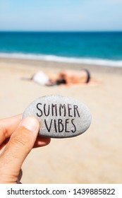 closeup of a caucasian man on the beach holding a stone, with the text summer vibes written in it, and some unrecognizable people relaxing and the sea in the background
