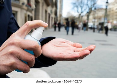 closeup of a caucasian man on the street disinfecting his hands with a blue hand sanitizer from a bottle