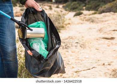 closeup of a caucasian man outdoors collecting garbage with a trash grabber stick, as an action to clean the natural environment