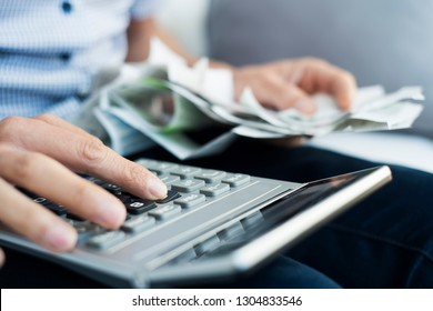 closeup of a caucasian man with a pile of bills and tickets in his hand using an electronic calculator to do some accounts