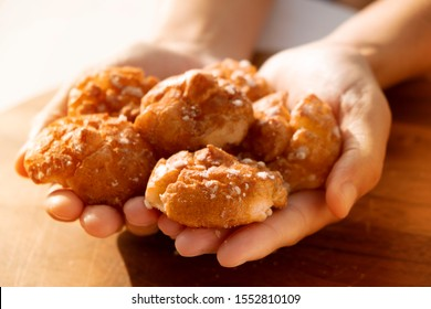 closeup of a caucasian man with some chouquettes, pastries typical of France, in his hands