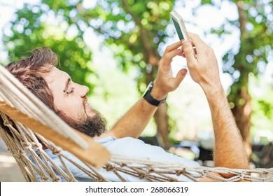 closeup of a caucasian man using mobile phone white swinging in