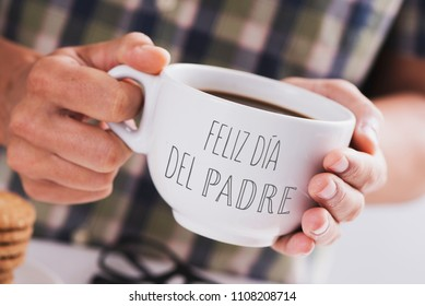 closeup of a caucasian man with a white ceramic cup with coffee in his hands, with the text 'feliz dia del padre', 'happy fathers day' written in spanish, at a table set for breakfast