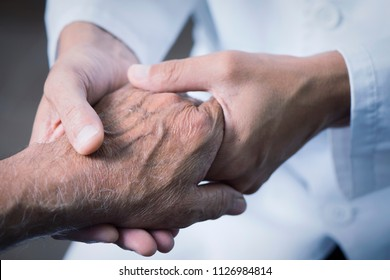 closeup of a caucasian man, in a white coat, moving the hand of a senior caucasian patient man