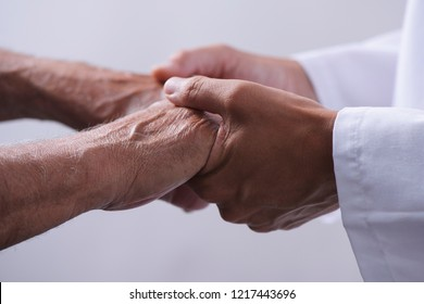 closeup of a caucasian man, in a white coat, holding the hands of a senior caucasian man