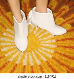 Close-up of Caucasian mid-adult female feet in white vintage boots against sunburst rug.
