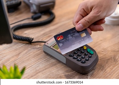 Closeup of Caucasian right hand, holding a black credit card on a POS terminal