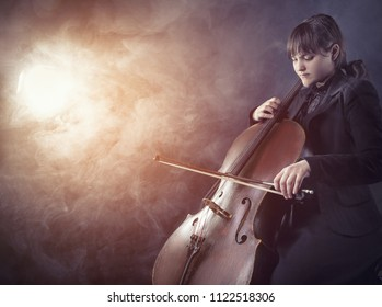 Close-up of cellist playing classical music on cello against a black background. Fog in the background. Studio shot