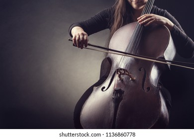 Close-up of cellist playing classical music on cello on black background