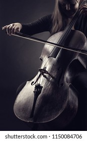 Close-up of cellist playing classical music on cello against a black background