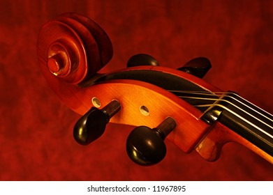 Close-up of cello scroll, with warm tones against canvas background.