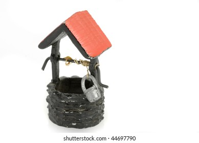 Closeup of a ceramic model of an old well.  Stone walls and red roof isolated on white background.