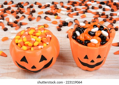 Closeup of a ceramic pumpkin shaped bowl and bucket filled with candy corn and jelly beans. Horizontal format on a white rustic wood table with loose candy strewn in the background.
