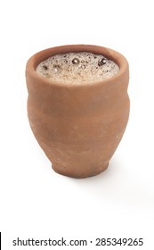 Close-up of chai in traditional cup made of mud isolated over white background