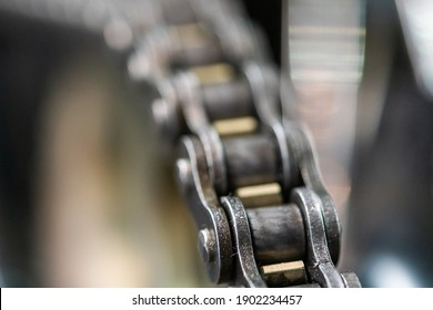 Close-up of a chain drive on a motorbike. shiny metal