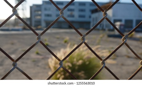 Closeup chain link fence with view across barren yard to derelict buildings. Abstract image for bleakness, melancholy, desolation.