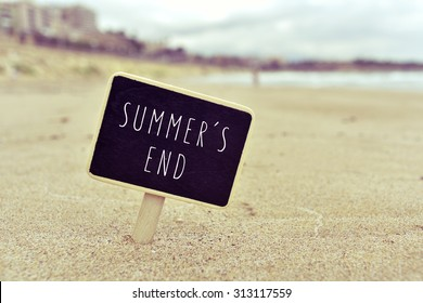closeup of a chalkboard with the text summers end written in it, in the sand of a lonely beach