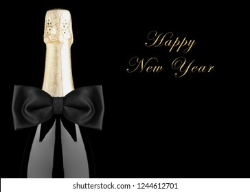 Closeup of a Champagne Bottle with Black Bow Tie isolated on black background with Happy New Year.