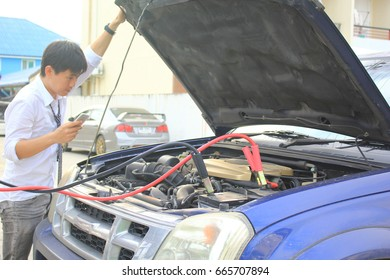 Close-Up Of Charging automobile discharged battery and Man calling to car mechanic service