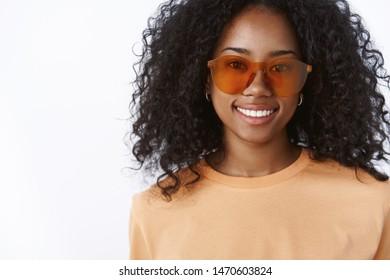 Close-up charming fashionable stylish dark-skinned young female wearing awesome trendy sunglasses orange t-shirt enjoying vacation tourist walking downtown feel happy smiling broadly