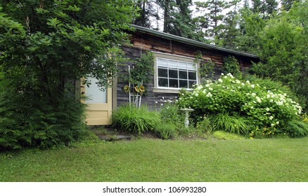 closeup of a charming wood house with flower garden