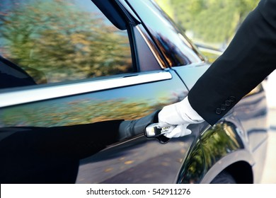 Closeup of chauffeur opening car door