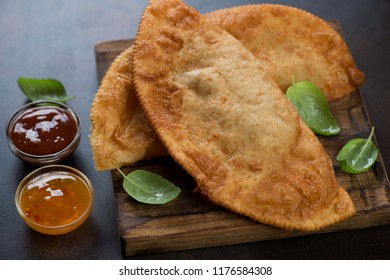 Close-up of chebureki or deep-fried turnovers with a filling of minced meat and onion, studio shot