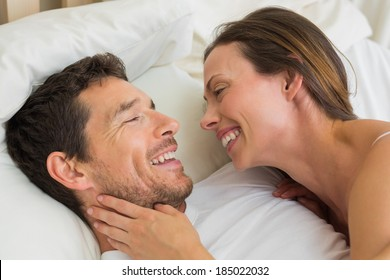 Close-up of a cheerful young couple lying together in bed at home