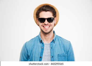 Closeup of cheerful young man in hat and sunglasses standing and smiling over white background