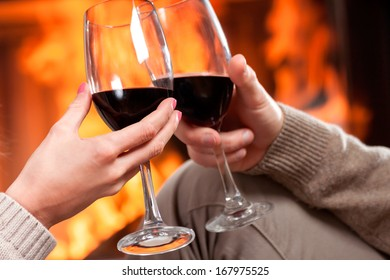 A closeup of cheering with glasses of red wine