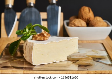 Close-up of cheese and walnuts on wood cheese board