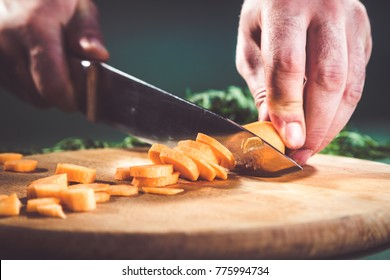 Close-up of chef carrot with kitchen knife on cutting board.