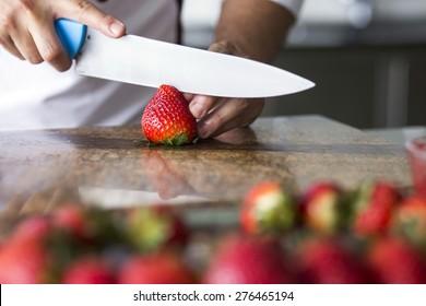 Closeup of a chef cutting strawberries