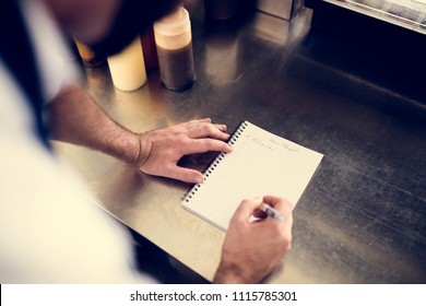 Closeup of chef hand writing menu on metal cooking table