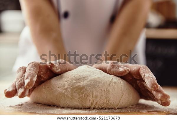 Nahaufnahme von Küchenhänden, die rohen Teig aus Holzbrett kneten. Backkonzept.