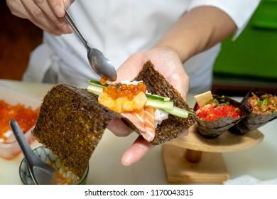 Closeup of chef hands preparing japanese food. Japanese chef making sushi at restaurant.