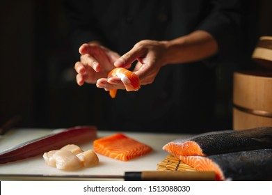 Closeup of chef hands preparing japanese food. Japanese chef making sushi at restaurant. Young chef making traditional japanese sushi on cuting board .